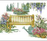 Сад с цветами и скамейка